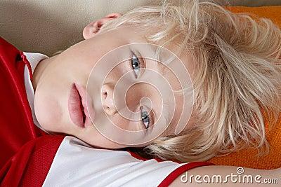 Kid laying down wearing soccer team tshirt.