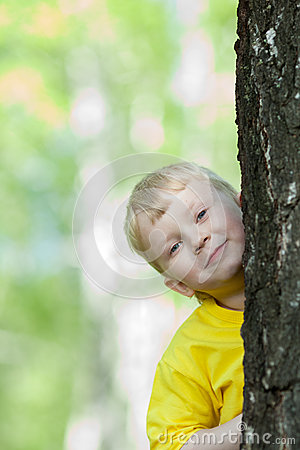 Kid looking from behind tree outdoor