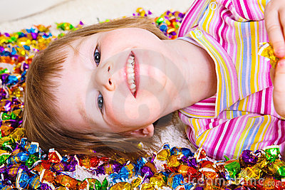 Kid lying among candies