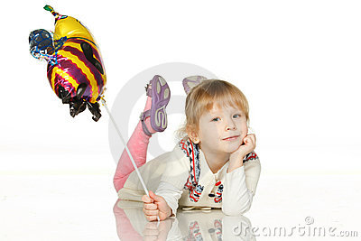 Kid lying on the floor with balloon bee