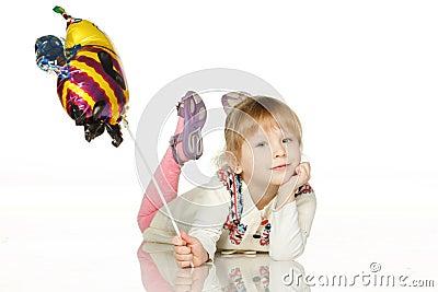 Kid lying on the floor with balloon bee