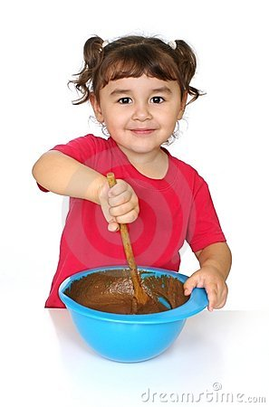 Three-year-old Hispanic girl mixing a bowl of chocolate cake batter ...