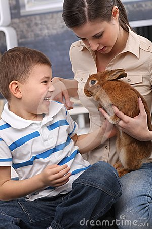 Kid and mom with pet rabbit at home