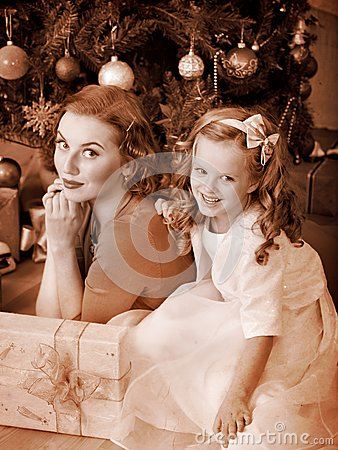 Kid with mother near Christmas tree.