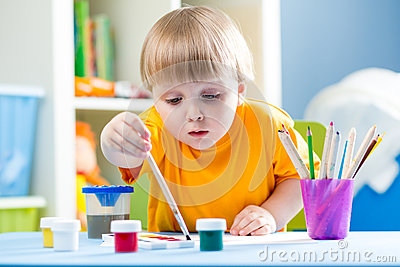 Kid painting at table in children room Stock Photo