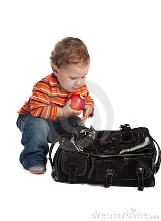 Kid with red apple, sitting near a bag, isolated