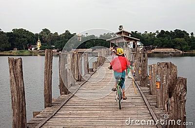 Kid riding bike on U-Bein bridge in Mandalay Editorial Photo