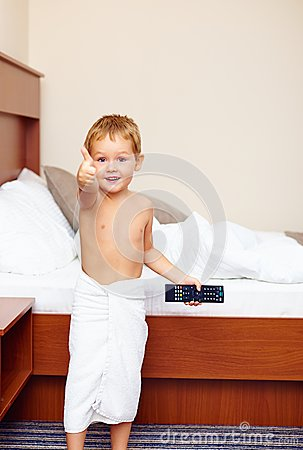 Kid showing thumb up in hotel room after bathing