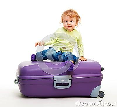Kid sit on the big suitcase