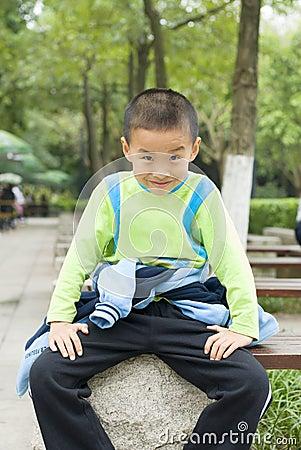 A kid sit beside tree