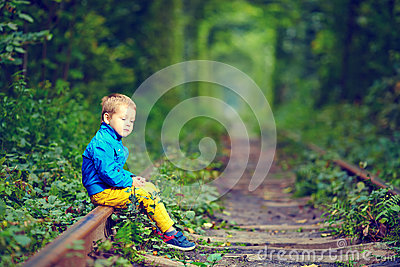 Kid sitting on rails in green tunnel