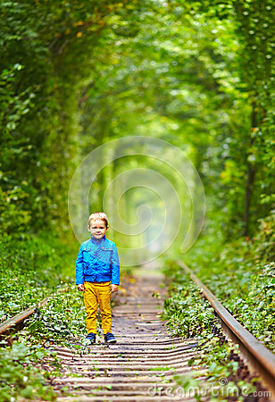 Kid walking the rails in green tunnel