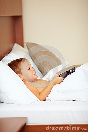 Kid watching entertainment tv shows in bed
