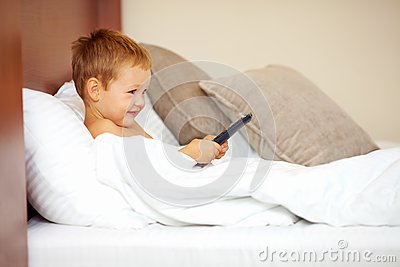 Kid watching tv cartoons in bed