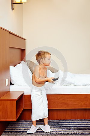 Kid watching tv in hotel room after bathing