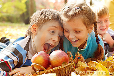 Kids biting autumnal apples