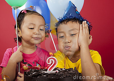 Kids blowing birthday candle