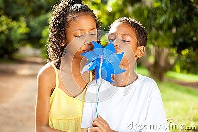 Kids blowing on a pinwheel