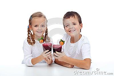 Kids clink glasses of fresh beetroot juice
