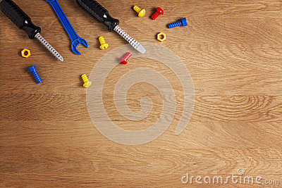 Kids construction toys tools: colorful screwdrivers, screws and nuts on wooden background. Top view. Flat lay. Stock Photo