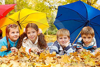 Kids group under umbrellas