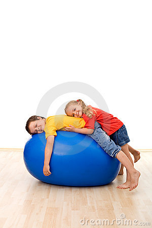 Kids having fun relaxing on a large rubber ball