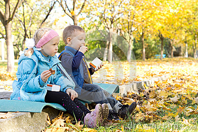 Kids having a snack in an autumn park