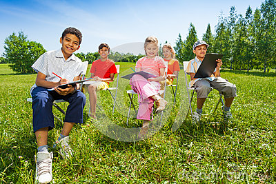 Kids hold sketch-boards and sit outside on chairs
