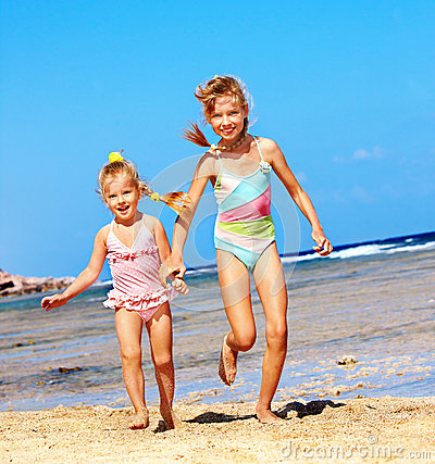 Kids holding hands running on  beach.