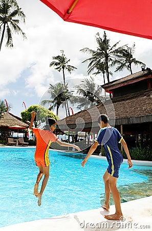 Kids jumping into resort pool