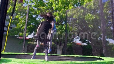 Kids jumping on trampoline, slow motion - 02. Two girls jumping on the trampoline on a sunny day. Shoot in slow motion stock video footage