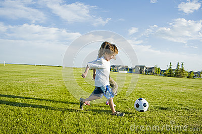 Kids kicking soccer ball