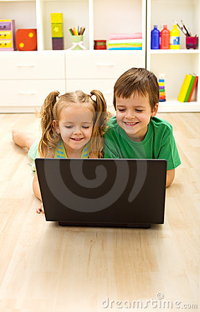 Kids with laptop laying on the floor