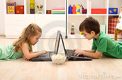 Kids with laptops and a bowl of popcorn