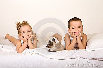 Kids laying in the bed with their kitten