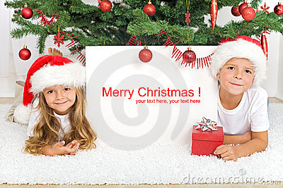 Kids laying under the christmas tree