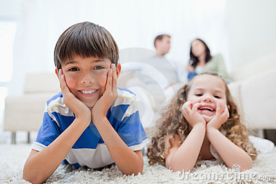 Kids Lying On The Carpet With Parents Sitting Behind Them