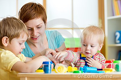 Kids and mother playing colorful clay toy Stock Photo