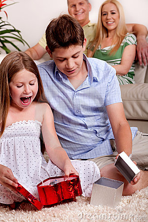 Kids opening christmas gifts with parents