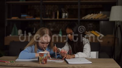 Kids painting with paintbrushes and watercolors stock footage