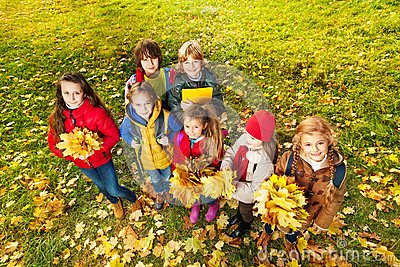 Kids in the park on autumn lawn