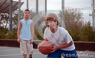 Kids play basketball in a school.