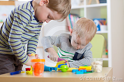 Kids Play Modeling Plasticine, Children Mold Colorful Clay Dough. Preschooler Playing Together Stock Photo