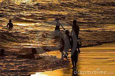Kids play in the surf at sunset