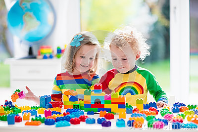 Kids playing with colorful plastic blocks Stock Photo
