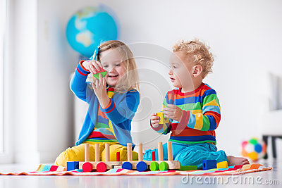 Children playing with wooden train. Toddler kid and baby play with ...