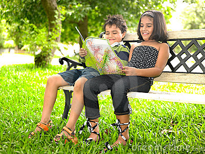 Kids reading a book in a park