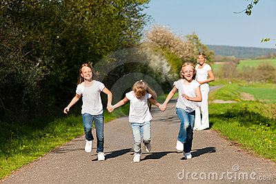 Kids running in spring, mother standing