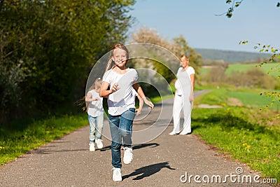Kids running in spring, mother standing