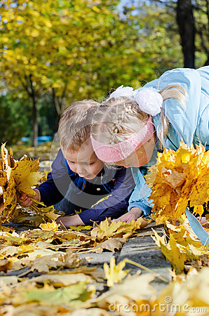 Kids searching amongst autumn leaves